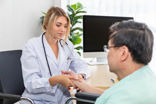 病室で年配の男性患者と脈を持っている女性白人専門医師の手。