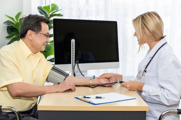 女性白人専門医師は病室で患者と血圧をチェックします。