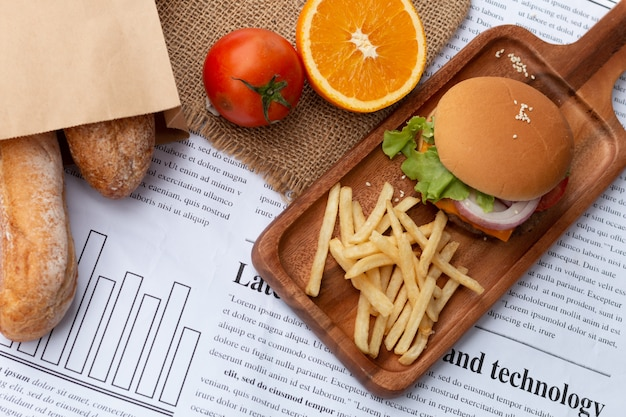 Меню завтрака. домашний бургер и картофель на деревянных возле газеты.