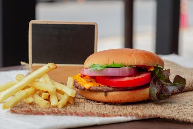 Свежий вкусный гамбургер и картофель на столе.