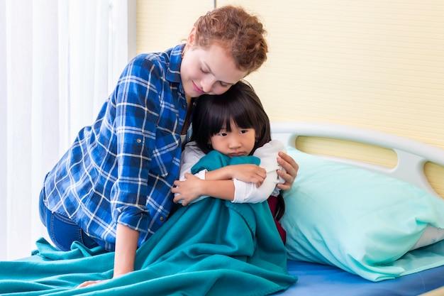 母は娘を安心させ、話し合う。寝室の病院で悲しい患者の女の子。