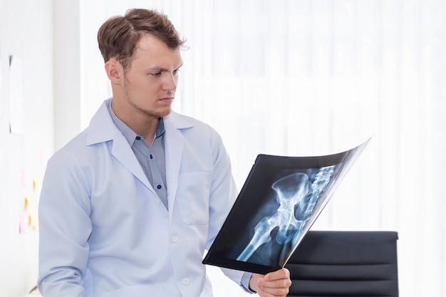 Медицинские работники кавказских человек, держащий рентген в комнате хопитал.