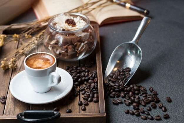暖かい朝の木製トレイにエスプレッソカップ、コーヒー豆、本、ドライフラワージャー。