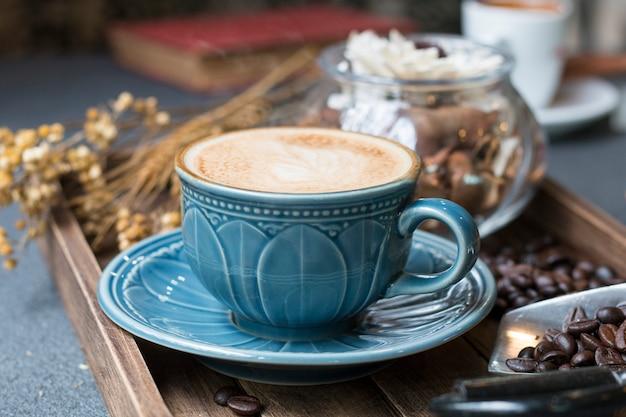 ラテカップ、コーヒー豆、本、暖かい朝の木製トレイにドライフラワージャー。