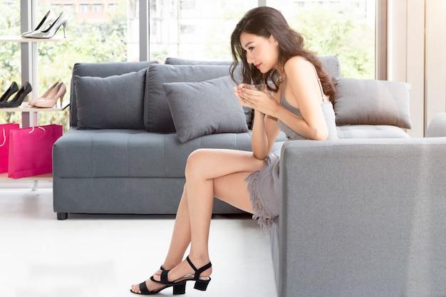 Молодая красивая женщина держа кофейную чашку и наслаждаясь в покупках на магазине одежды