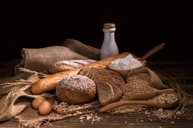 全粒小麦パン、牛乳、小麦粉、木のテーブルの上の布バッグ