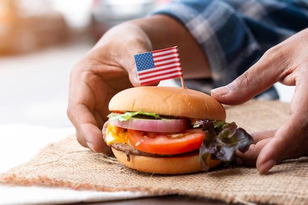 新鮮なおいしいハンバーガーを握っている人の手。