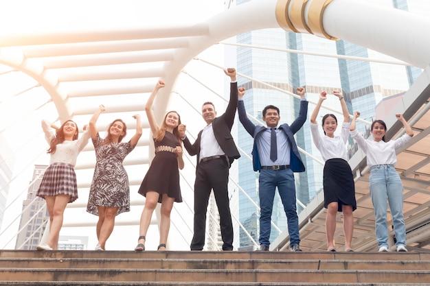 手を繋いでいるビジネスチームのグループは、ビジネスの成功を上げました。