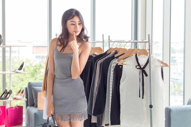 衣料品店で買い物を楽しんで買い物袋を持つ若い美しい女性。