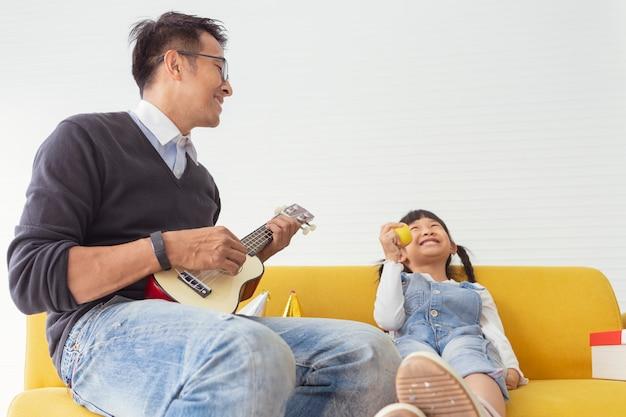 クリスマスの家族と幸せな休日の父は白いリビングルームで子供たちと現在の贈り物の近くでギターを弾きます。