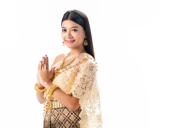 美しい女性は、タイの民族衣装で敬意を払います。白い背景に分離します。