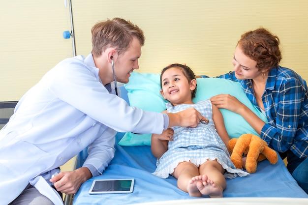 小児科医(医師)男は寝室の病院で聴診器を使用して小さな女の子の患者を調べます。