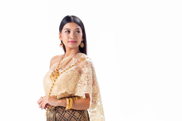 Красивая женщина усмехаясь в национальном традиционном костюме таиланда. изолировать
