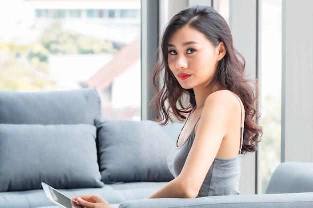 座っていると、リビングルームでタブレットでオンラインショッピングの美しい女性。