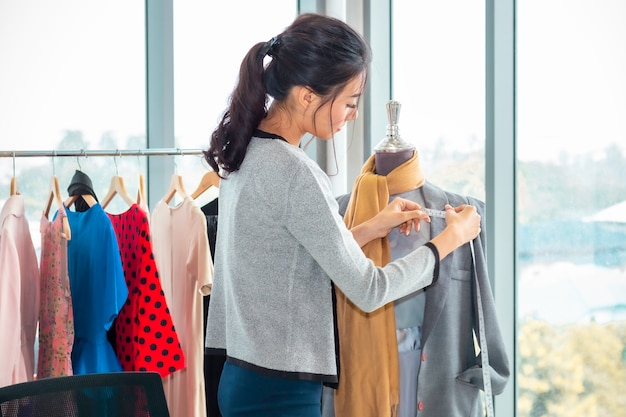 Стильная азиатская женщина модельер и портной работает в магазине одежды.