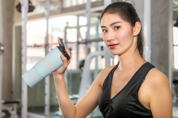 フィットネスジムでのエクササイズ後のスポーツウェア飲料水で若いアジア女性