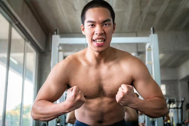 トレーニング後のジムで力強い筋肉のハンサムな男性が強く、健康的な笑顔