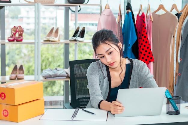 Счастливый малый бизнес предпринимателя запуска азиатской вскользь дамы работая в магазине одежды.