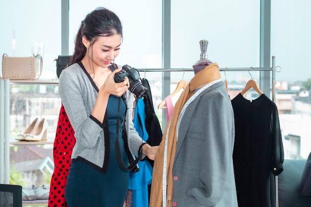 Молодая женщина азии красивая принимая фото и работая онлайн покупки электронной коммерции на магазине одежды.