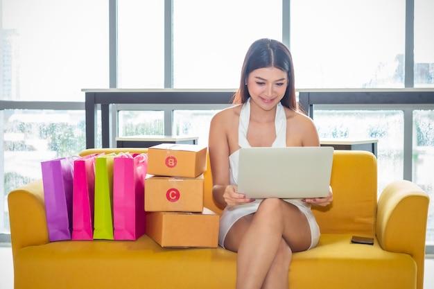 Молодая азиатская вскользь дама работая запуска предпринимателя малого бизнеса мсп в магазине одежды.
