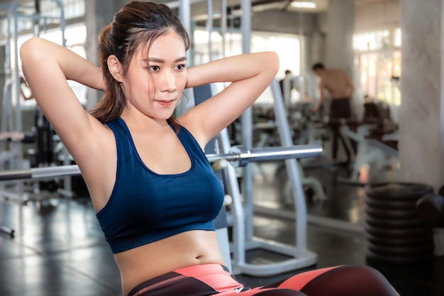 Совершенная азиатская женщина в тренировке спортивной одежды сидит вверх на спортзале фитнеса.