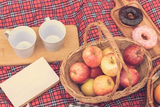 夏の時間。自然の中で食べ物や果物のピクニックバスケットのクローズアップ。