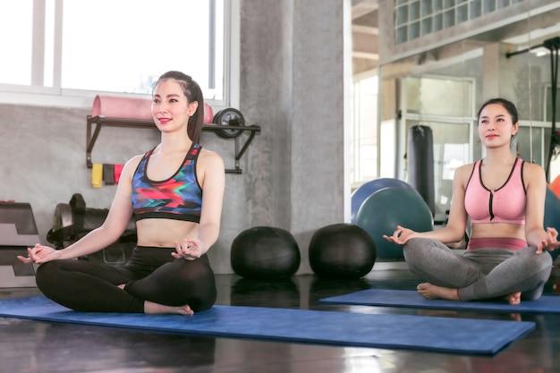 若いアジアの女性と友人がジムでヨガを練習します。ロータスは瞑想セッションでポーズします。