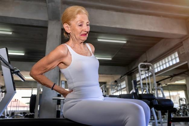 Боль в спине старшей женщины кавказская во время тренировки на спортзале фитнеса.