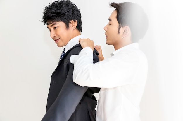 Азиатские гомосексуальные пары помогают друг другу одеваться. концепция лгбт геев.