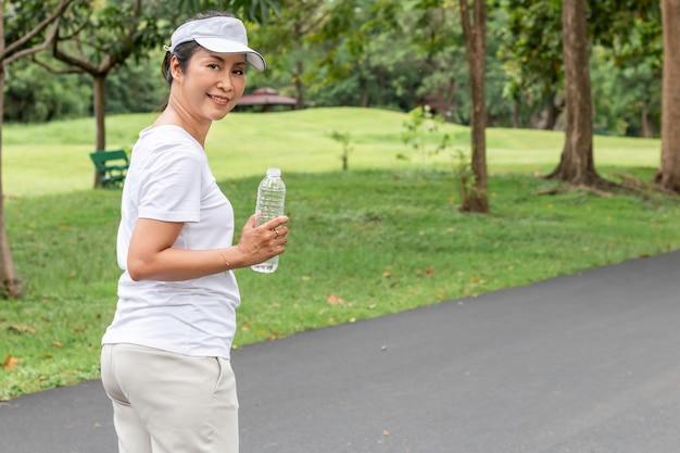 リラックスした時間。アジアの笑みを浮かべて年配の女性が公園で夏に新鮮な水を飲む。