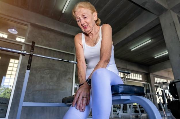 フィットネスジムでトレーニング中に年配の女性白人脚の痛み。