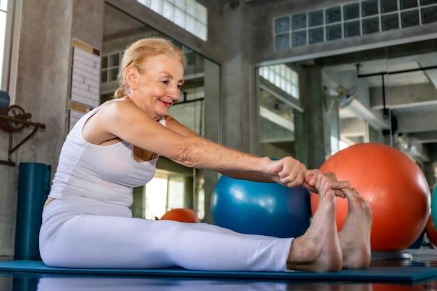 フィットネスジムでヨガの練習をしている白人の年配の女性。