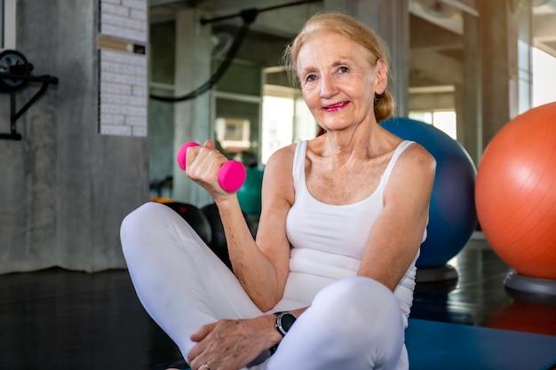 フィットネスジムでダンベルを持つ年配の女性白人トレーニングアーム。