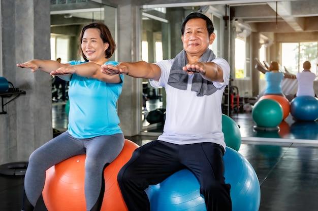 ジムで運動スポーツウェアに笑みを浮かべてアジアシニアカップル。