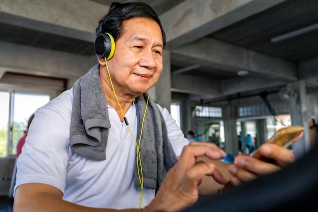 スポーツウェアのシニアアジア人は、フィットネスジムで音楽やトレーニングサイクリングカーディオに耳を傾けます。