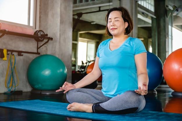 Йога старшей тучной женщины азиатская делая тренировку йоги на спортзале фитнеса.