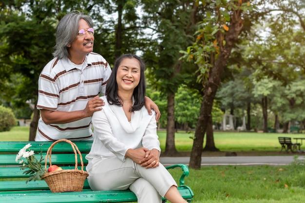 Азиатские старшие пары с счастьем образа жизни корзины плодоовощ в парке.