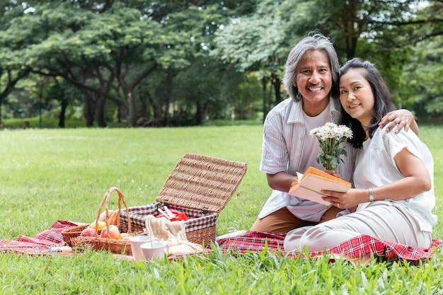年配のカップルはリラックスして公園でピクニックします。妻は私の夫に花を与えます。