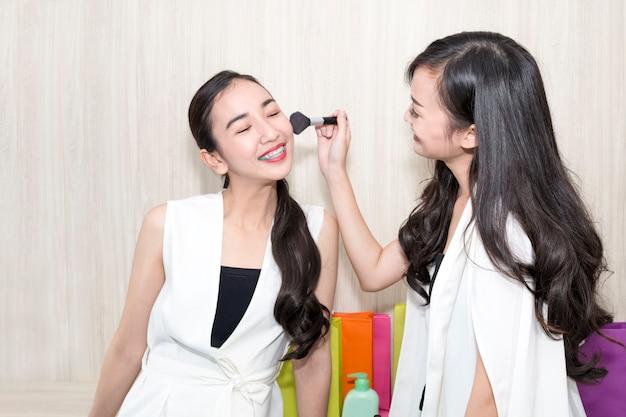 出荷のための顔を持つ若い美しい女性の友情テスト化粧品。