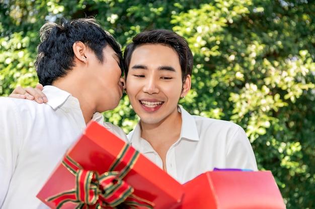 愛の甘い瞬間。アジアの同性愛カップルの抱擁と彼氏へのサプライズボックスギフトの肖像画