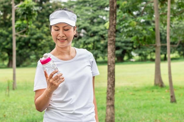 公園で夏に新鮮な水を飲んで笑っているアジアの高齢女性。