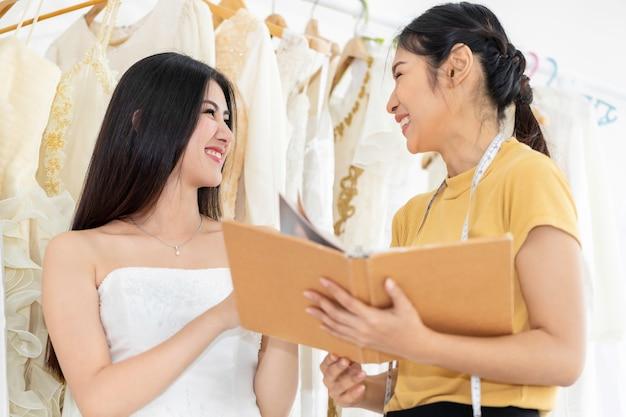 Довольно азиатская женщина выбирая платье в магазине с ассистентом портноя.
