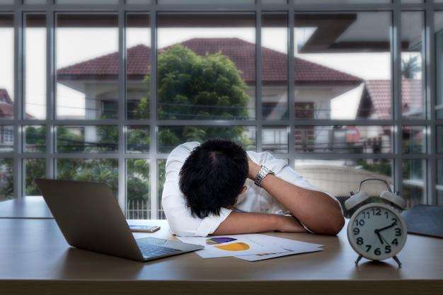 Молодой бизнесмен спать и перегружанный около компьтер-книжки на офисе.