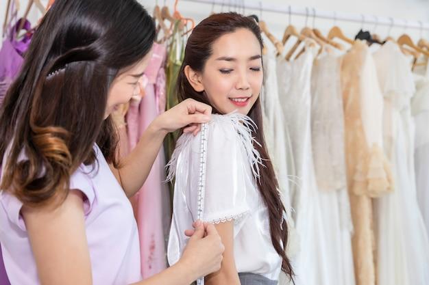 Портрет азиатской женщины выбирая платье в магазине с ассистентом портноя.