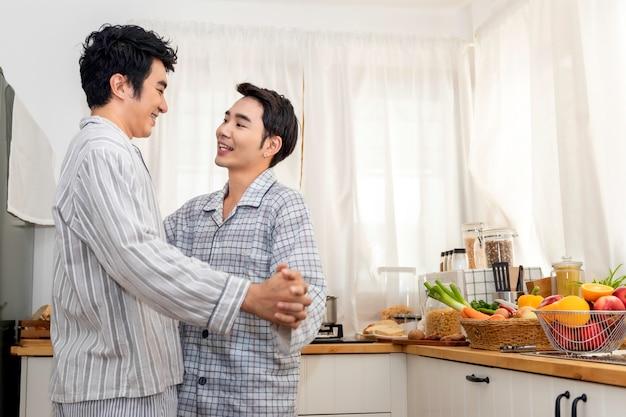 アジアの同性愛者のカップルが抱擁し、朝のキッチンでキス