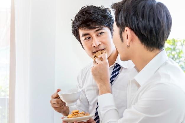 リラックスしてティータイム。クッキーを食べて面白い瞬間を楽しむアジアの同性愛カップルの肖像画