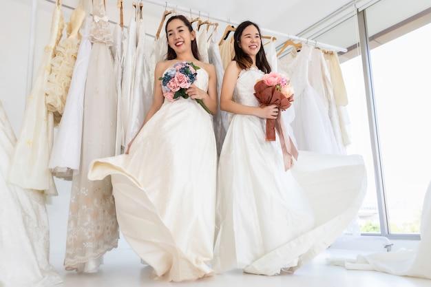 Две невесты белые платья. портрет азиатской гомосексуальной пары, счастливой в момент свадьбы. концепция лгбт-лесбиянок.