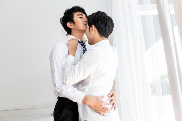 愛の甘い瞬間。仕事の前に夫にキスするアジアの同性愛カップル