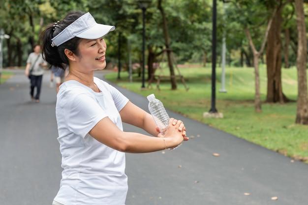 公園で夏に新鮮な水を飲むボトルと古いアジアの女性。