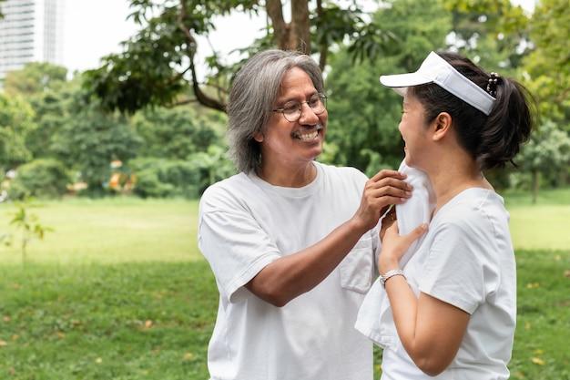 スポーツウェアのアクティブなアジアのカップルが公園で運動した後、汗を拭いています。